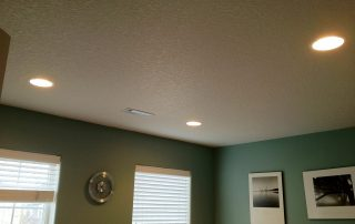 green wall with recessed lighting in ceiling